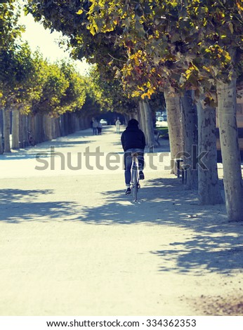A man is riding a bike in the streets on a summer day in Germany.  Image has a strong vintage effect applied. - stock photo