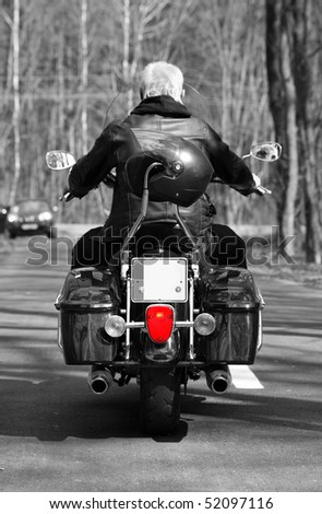 A man is riding a motorbike on the forest road (view from behind) - stock photo