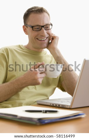 A man is seated at a computer desk and is working on a laptop.  He is enjoying a cup of coffee.  Vertical shot.  Isolated on white. - stock photo