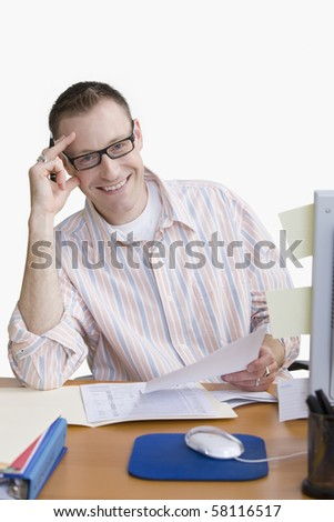 A man is seated at a computer desk and smiling at the camera.  Vertical shot.  Isolated on white. - stock photo