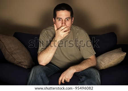 A man is shocked by what he sees on the television - stock photo