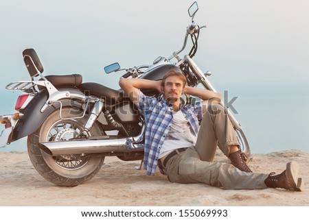 A man is sitting on the beach with his back to the bike. - stock photo
