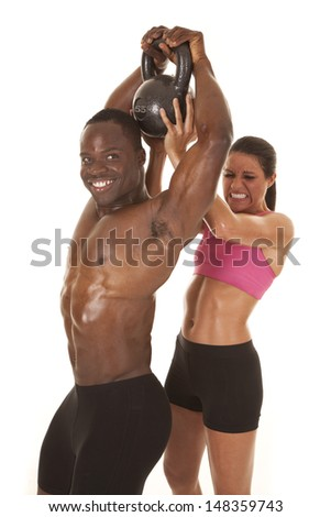 A man is smiling while a woman is behind him working to lift the weight - stock photo