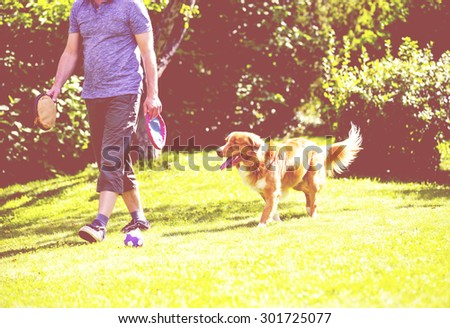 A man is teaching and training the dog outdoor in the park. The dog breed is nova scotia duck tolling retriever. Composition is so to emphasize the situation of teaching. Image has a vintage effect - stock photo