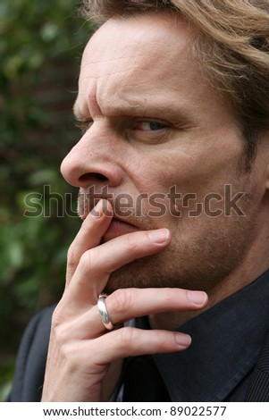 A man is thinking over something.  He has his thinking face on. - stock photo