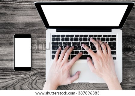 A man is typing on laptop keyboard. Mock up screens for laptop and smartphone. Top view. - stock photo