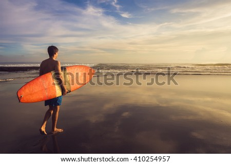 A man is walking with a surf in his hands across the ocean shore.  - stock photo