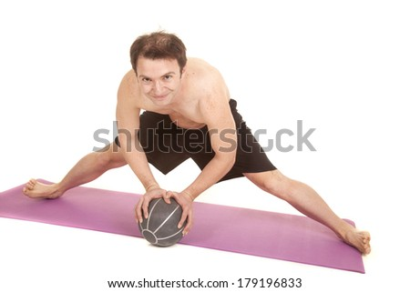 A man is working out with a medicine ball doing the splits. - stock photo