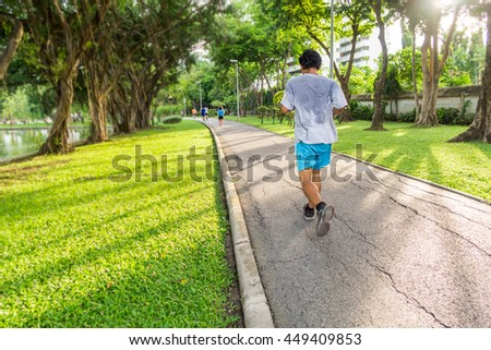 A man jogging in the park beside the lake,in the evening light  - stock photo