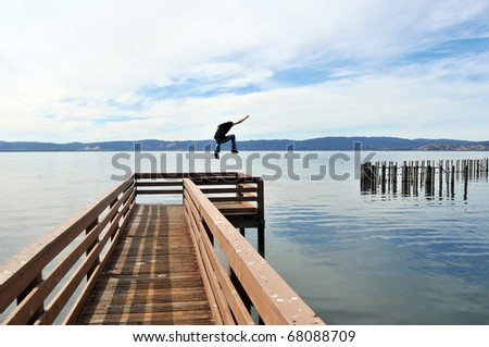 A man jumping a long narrow wooden pier into the calm blue ocean water with outstretched victorious arms. - stock photo