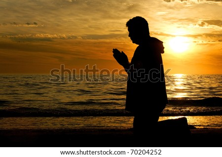 A man kneeling on the beach and praying in front of a golden sunset. - stock photo