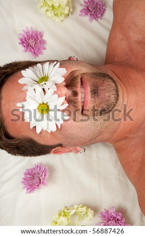 A man lies on a massage table with flowers over his eyes. - stock photo