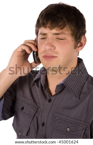 A man listening on the phone with an upset expression on his face. - stock photo