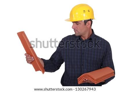 A man looking at tiles. - stock photo