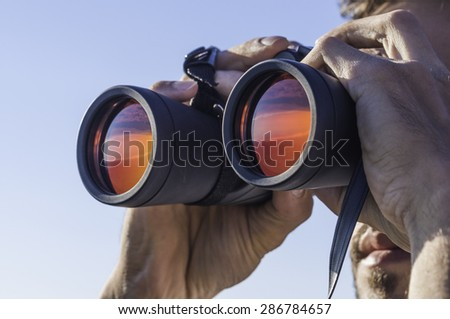 A man looking through the binoculars  - stock photo