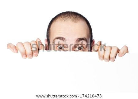 A man looks surprised to looking out for a poster on which you can write an inscription. - stock photo