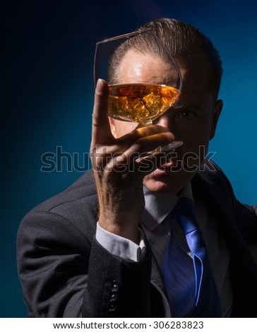 A man looks through the glass of cognac - stock photo
