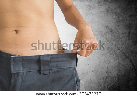 A man loose their weight, healthy diet concept, with concrete texture background - stock photo