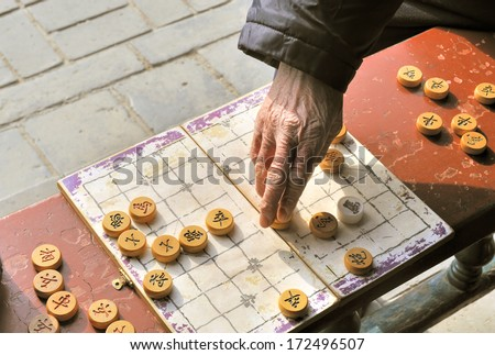 A man makes a move on a on a local Beijing Chinese chess game board. Xiangqi, also known as Chinese chess, is an ancient board game played all over the world. - stock photo