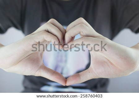 A Man Making Heart Shaped Hand Gesture - stock photo