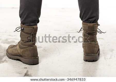 A man(male, boy) wearing khaki(brown) military shoes(combat military boots) and cargo pants at the studio. - stock photo