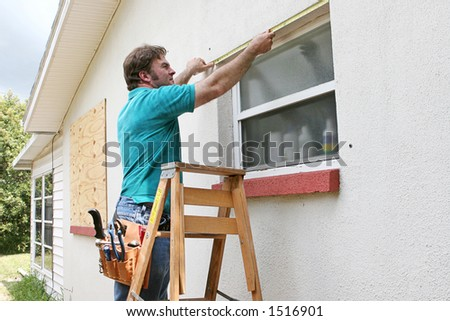 A man measuring windows for hurricane shutters or plywood. - stock photo