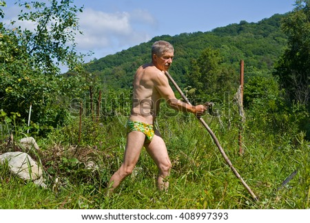 A man mows a grass with a scythe on green meadow. Summer, sunny day. - stock photo