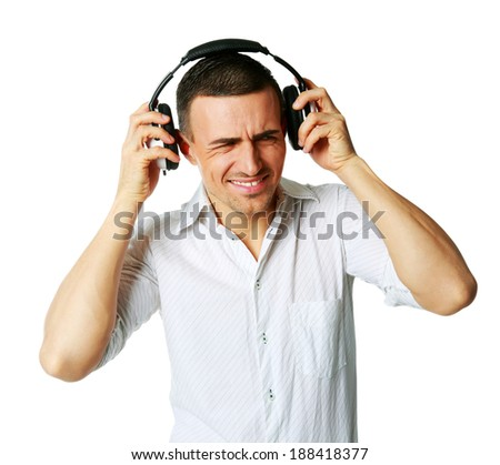 A man not enjoying what he is hearing, listening to music over white background - stock photo