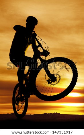 A man on a bike is silhouetted with the front tire popped up. - stock photo
