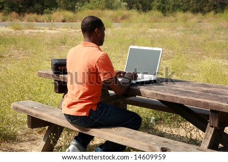 a man on a laptop computer outside in a park representing wireless connections and mobile business concepts - stock photo