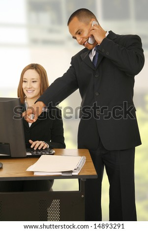 a man on the phone while pointing at computer screen while the other business woman looking at the screen and smiling. concept for business communication, or team work - stock photo