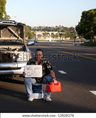 """a man out of gas holds an empty gas can and a """"will work for gas sign"""" - stock photo"""