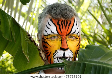 A man painted as a tiger, half hidden behind tropical leaves. - stock photo