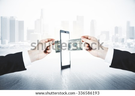 A man passes another man money through smartphone, online money transfer concept - stock photo