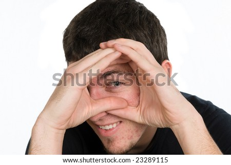 A man peering through his hands isolated on white. - stock photo