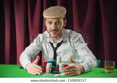 A man playing  Poker collects his winnings  - stock photo