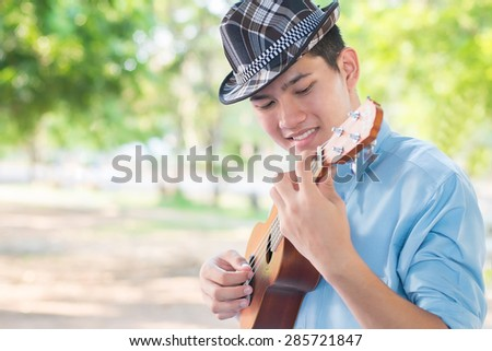 A man playing ukulele so happiness in park. - stock photo