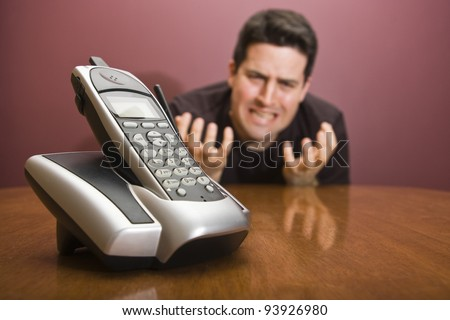 A man pleads for the phone to ring - stock photo