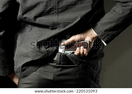 A man, policeman or gangster, concealing his gun behind his back - stock photo