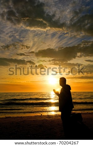 A man praying at the ocean while watching a glorious sunset. - stock photo