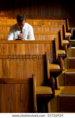 A man praying in church - stock photo