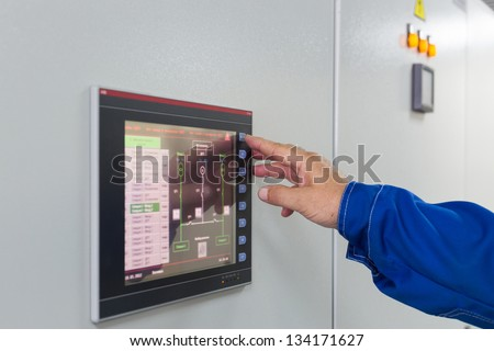 A man presses a button on color screen control of equipment for telecom. - stock photo