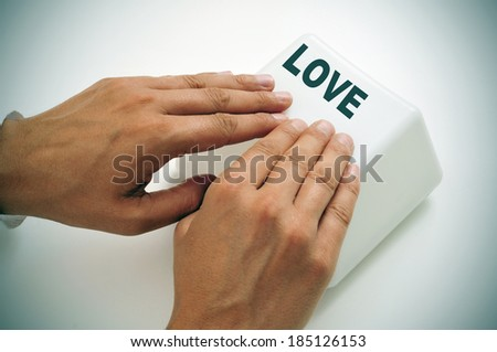 a man pressing a giant key with the word love written in it, depicting the idea of online dating or the need or search of love - stock photo