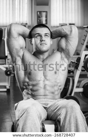 A man pumping abdominal muscles in the gym. Sports. Cubes abdominals. Exercises in the gym. - stock photo