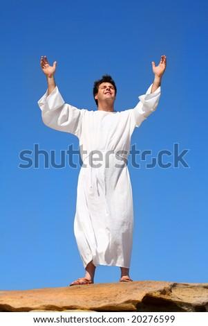 A man raises his arms  heavenward in an act of praise or worship - stock photo
