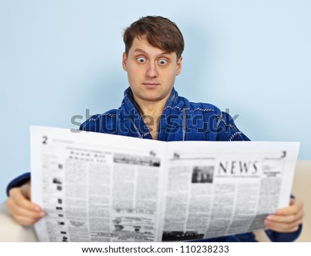 A man reads a newspaper with a amazement - stock photo