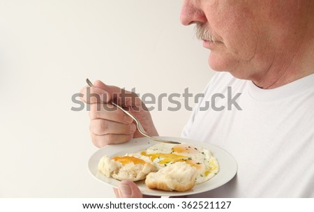 A man ready to eat his fried eggs breakfast - stock photo
