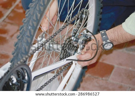 A man repairs the wheel of a bicycle with the hands and one adjustable spanner. Bike repair - stock photo