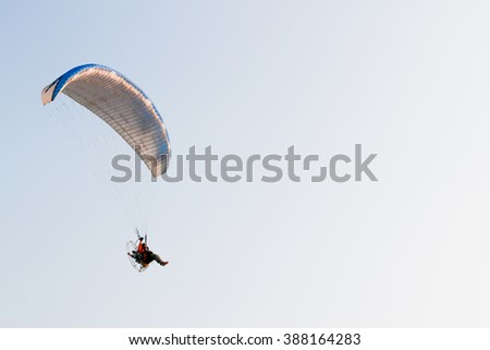 A man ride Paraglider or Paramotor flying in the sky - stock photo