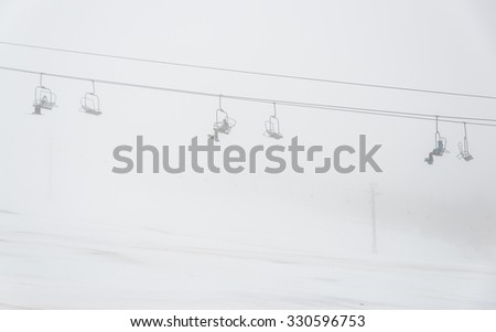 a man ride the ski chair lift up to the mountain in ski resort in Washington,USA. - stock photo